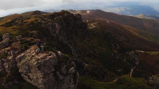 視差ショット:マウンテンバイカーは、風景を鑑賞するために山の頂上の石に少し時間がかかります - クロスカントリーサイクリング点の映像素材/bロール