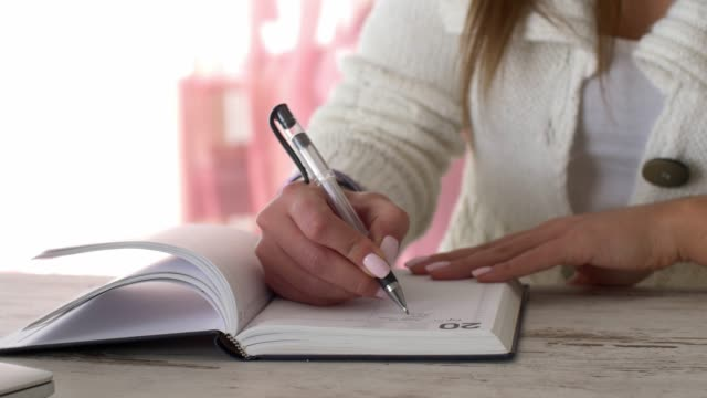 parallax shot of unrecognizable young female writing to do list in her diary - diary stock videos & royalty-free footage