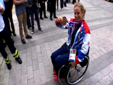Paralympian bronze champion Lucy Shuker wheelchair tennis player shows her medal before joining Team GB for the bus parade