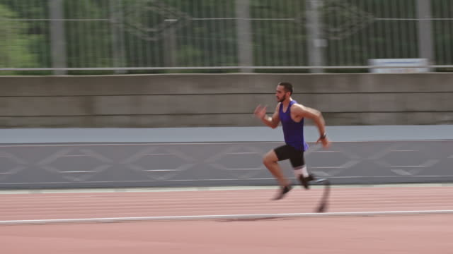 paralympic athlete with prosthetic leg running on track - amputee stock-videos und b-roll-filmmaterial