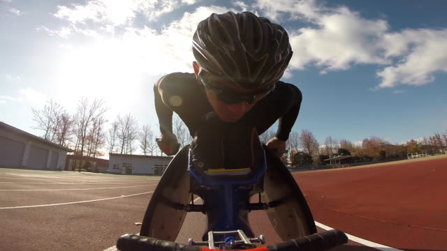 a paralympic racer speeds by on a track in his specialty wheelchair - adaptive athlete stock videos and b-roll footage