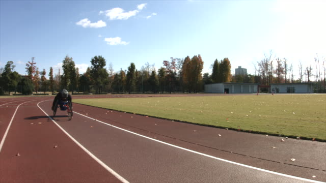a paralympic racer speeds by on a track in his specialty wheelchair - ランニングトラック点の映像素材/bロール