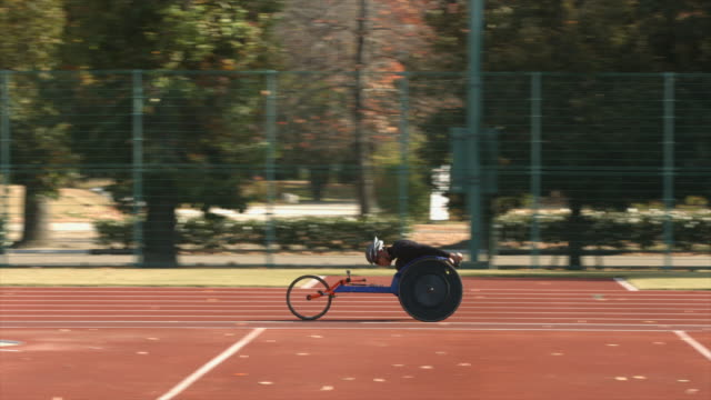 a paralympic racer speeds by on a track in his specialty wheelchair - 車いす点の映像素材/bロール
