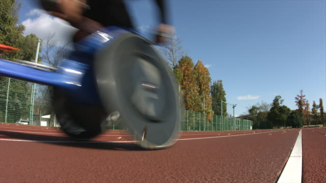 a paralympic racer speeds by on a track in his specialty wheelchair - wheelchair stock videos and b-roll footage