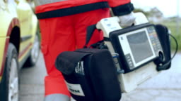 MS Paramedic carrying a portable defibrillator