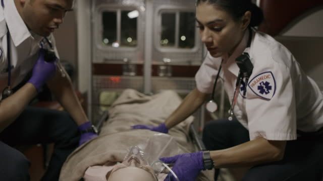 vídeos de stock e filmes b-roll de paramedic comforting and talking to patient in ambulance / lehi, utah, united states - lehi