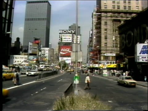 paramedic emergency squad van drives away from camera / view of times square looking north traffic moving towards camera / coca cola and sony signs... - times square manhattan bildbanksvideor och videomaterial från bakom kulisserna