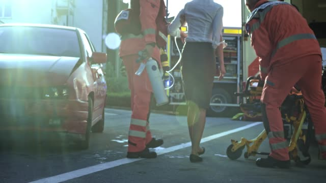 paramedic helping an injured woman walk to the stretcher at the scene of the accident so they can provide care - oxygen mask stock videos and b-roll footage