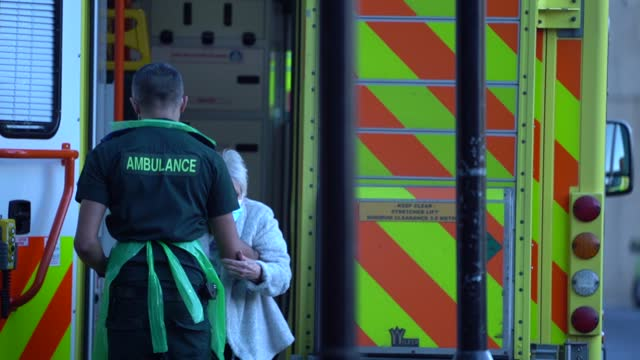 paramedic helps an elderly person as a row of ambulances are outside the emergency department of the royal london hospital in london, england, on... - slow motion stock videos & royalty-free footage