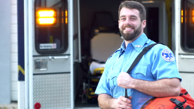 paramedic standing in front of ambulance - heroes stock videos & royalty-free footage
