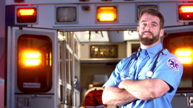 vídeos de stock e filmes b-roll de paramedic standing in front of ambulance - bigode