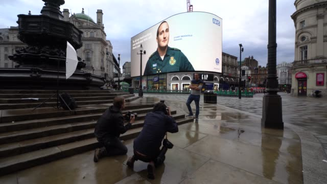 paramedic stuart brookfield poses for photographers as her image is displayed on the screens at piccadilly circus for the nhs #makeitblue campaign... - rescue worker stock videos & royalty-free footage