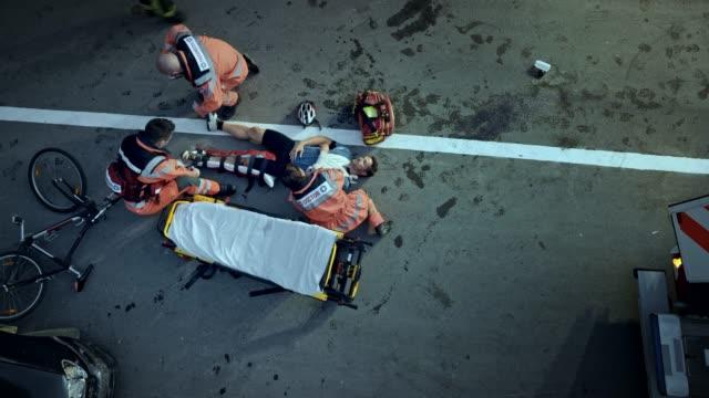 cs-sanitäter-team ruhigstellung des verletzten radfahrers bein und die versorgung, wie er auf dem boden liegt - rettungssanitäter stock-videos und b-roll-filmmaterial