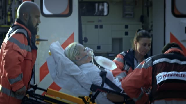paramedic team loading an injured woman on the stretcher into the ambulance with help from the firefighters - stretcher stock videos & royalty-free footage
