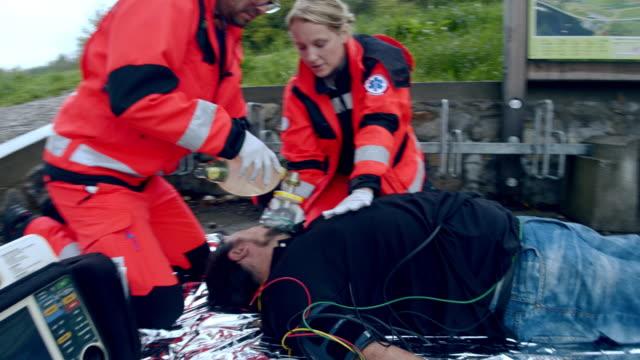 vidéos et rushes de équipe d'ambulanciers paramédicaux ws effectuant une rcr - secouriste