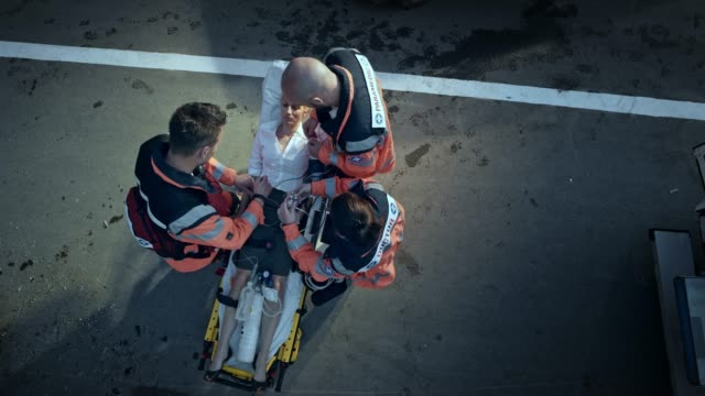 CS Paramedic team stabilizing the injured woman on the stretcher at the scene of the accident