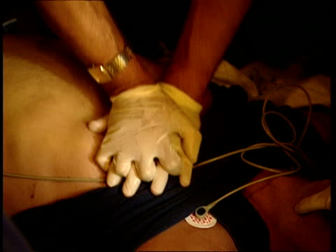 vídeos de stock, filmes e b-roll de mcu paramedic trying to revive man by cpr, tilt up to ecg machine - ataque cardíaco