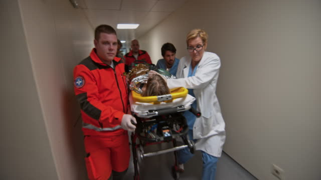 Paramedics and a medical team rushing a drowned child to the trauma room