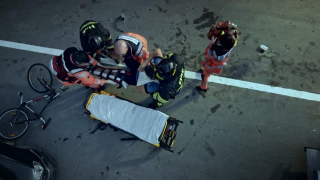 CS Paramedics and firefighters raising an injured male cyclist onto the stretcher at the scene of the accident