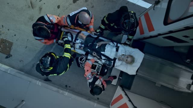 cs paramedics and firemen loading the female car accident victim on the stretcher into the ambulance - rescue worker stock videos and b-roll footage