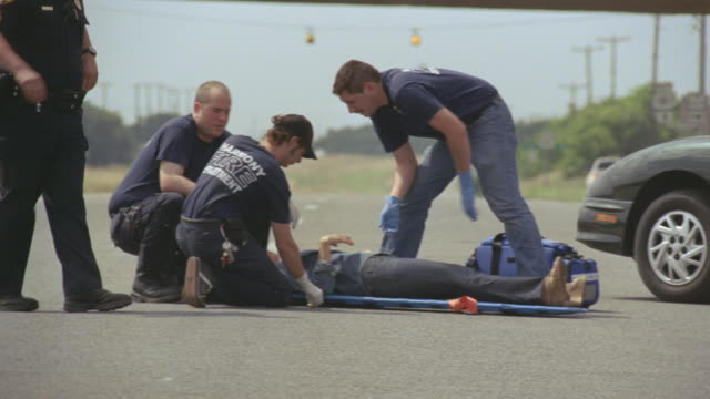 WS Paramedics assisting woman lying on stretcher after car accident / Elmendorf, Texas, USA