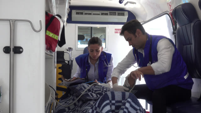 paramedics attending an unconscious patient - paramedic stock videos & royalty-free footage