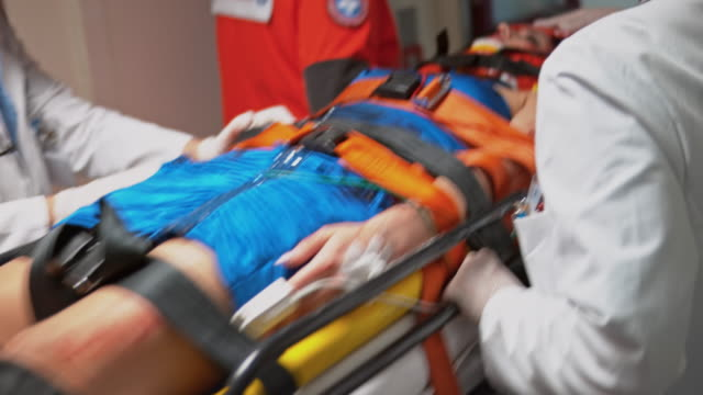 paramedics bringing an injured woman into the emergency room - emergencies and disasters stock videos and b-roll footage