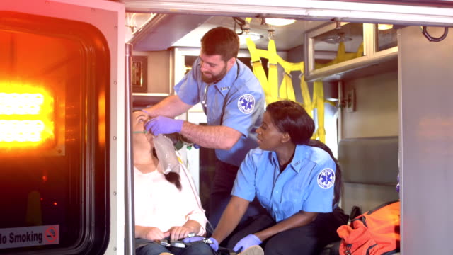 paramedics care for patient inside ambulance - paramedic stock videos & royalty-free footage