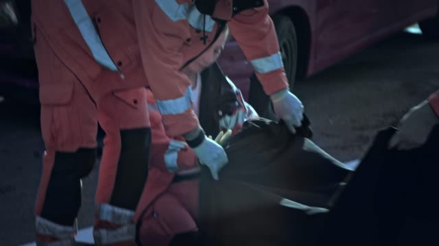 paramedics covering the body of a young woman at the scene of a car accident - three people stock videos & royalty-free footage