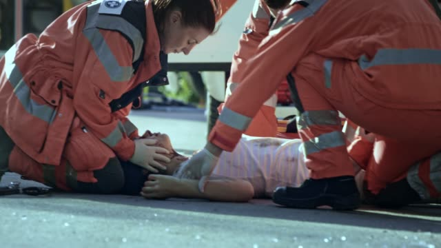 vídeos de stock e filmes b-roll de paramedics declaring death of a young woman lying injured on the ground at the scene of a car accident - impacto