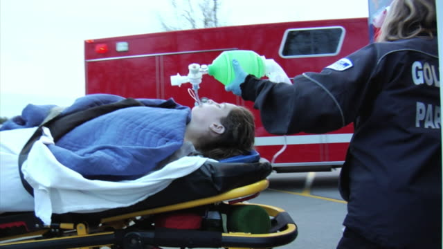MS Paramedics getting ready to lift stretcher with unconscious girl (14-15) into ambulance, New London, Wisconsin, USA
