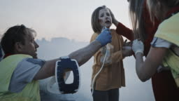 Paramedics Giving First Aid Oxygen Mask to a Young Girl Victim of the Accident. Professionals Saving Lives. Smoke Everywhere