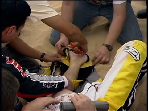 cu, ms, zi, zo, composite, paramedics immobilizing leg of injured motocross rider lying on sand, imperial sand dunes, california, usa - 一分鐘或更長 個影片檔及 b 捲影像