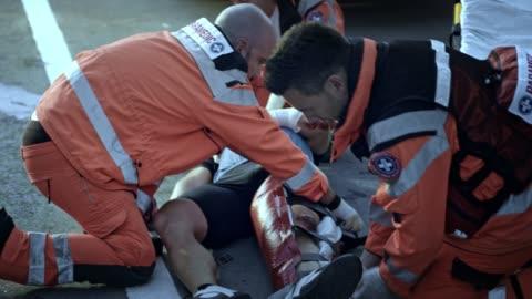 stockvideo's en b-roll-footage met paramedici immobilizing de gewonde fietser been op de brancard - reddingswerker