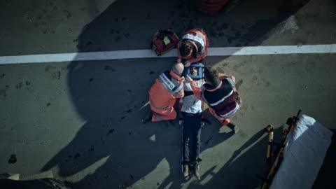 vídeos y material grabado en eventos de stock de cs paramédicos inmovilizando la cabeza del hombre herido sobre la camilla en la escena del accidente de coche - accidente de tráfico