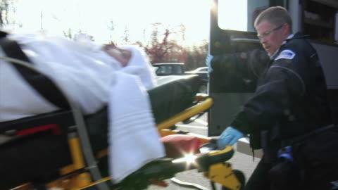 stockvideo's en b-roll-footage met ms paramedics lifting man on stretcher into ambulance, new london, wisconsin, usa - reddingswerker