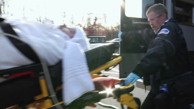 MS Paramedics lifting man on stretcher into ambulance, New London, Wisconsin, USA