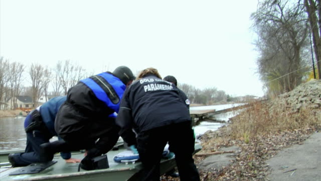 MS Paramedics lifting unconscious girl (14-15) from boat and walking towards land, New London, Wisconsin, USA