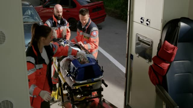 paramedics loading a man injured in a car accident into the ambulance - paramedic stock videos & royalty-free footage