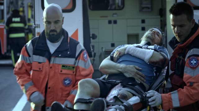paramedics loading the injured male cyclist in the ambulance at the scene of the accident - paramedic stock videos & royalty-free footage