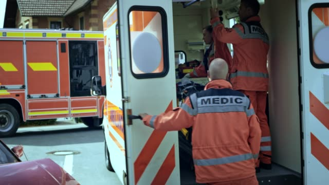 paramedics loading the injured person into the ambulance and closing the door - stretcher stock videos and b-roll footage