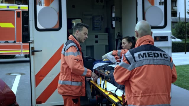 paramedics loading the injured person into the ambulance - stretcher stock videos and b-roll footage