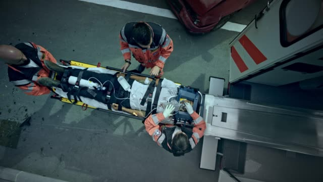 stockvideo's en b-roll-footage met cs paramedici laden de gewonde vrouw op de brancard naar de ambulance - mid adult men