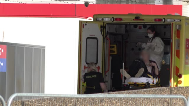 paramedics lower a patient on a gurney from and an ambulance and wheel him towards pulls the accident and emergency entrance at st thomas' hospital,... - boris johnson stock-videos und b-roll-filmmaterial