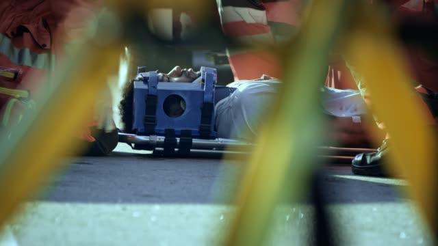 ds-sanitäter, die den kopf eines jungen mannes verletzt bei einem unfall in einem kopf wegfahrsperre - rettungssanitäter stock-videos und b-roll-filmmaterial