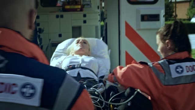 paramedics preparing an injured woman on the stretcher for an ambulance transport - stretcher stock videos & royalty-free footage