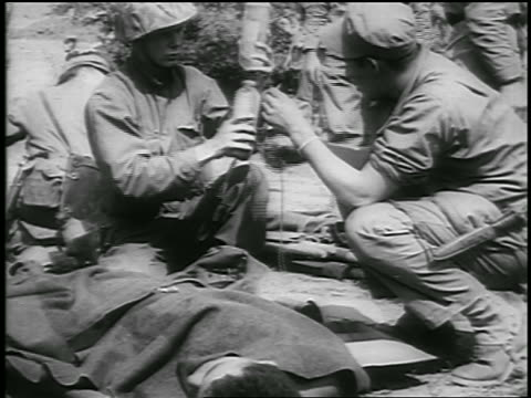 b/w 1950 paramedics preparing iv for wounded soldier in korean war / newsreel - korean war stock videos & royalty-free footage