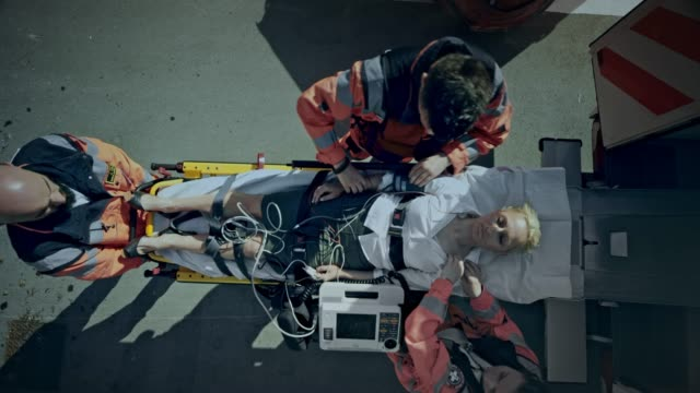 cs paramedics preparing the injured woman on the stretcher for transport and loading her into the ambulance - stretcher stock videos & royalty-free footage