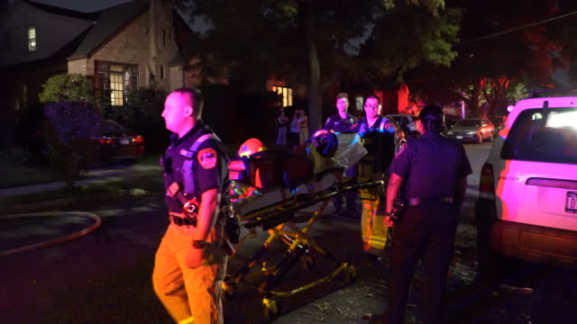Paramedics pushing a gurney respond to a house fire in Rego Park New York