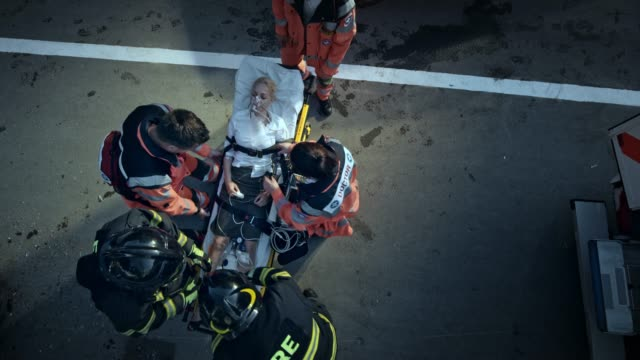 vídeos de stock e filmes b-roll de cs paramedics securing the injured woman on the stretcher for transport with the help of the firemen - resgate